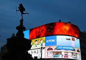 Näyttävimmillään (jo ennen uutta LED-aikakautta) Piccadilly Lights esittäytyy pimeällä. Aukion vetovoimainen nähtävyys on myös silhuettina näkyvä Eros-patsas. Kuva: Kai Aulio.