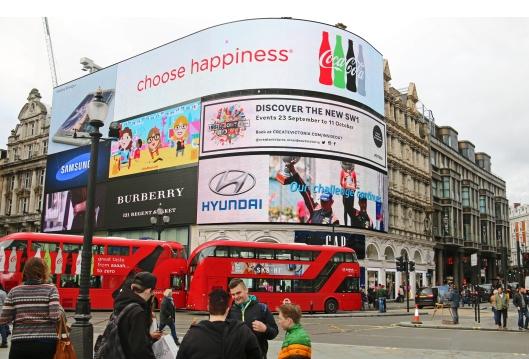 """Piccadilly Circus on Lontoossa paitsi """"pakollinen nähtävyys"""" myös suosittu ja turvallinen kokoontumispaikka. Aukion mainokset ovat värikkäitä jopa pilvisenä päivänä, ilman sähkövaloja. Kuva: Kai Aulio."""