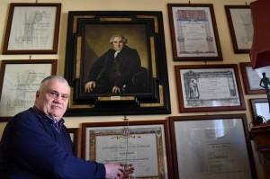 Luciano Baietti ja 15 todistusta yliopistotutkinnoista, kehystettyinä 1800-luvulla eläneen kirjailijan Louis-Francis Bertinin – opiskelijan tärkeän innoittajan – muotokuvan ympärille. Kuva: Alberto Pizzoli, AFP via The National.